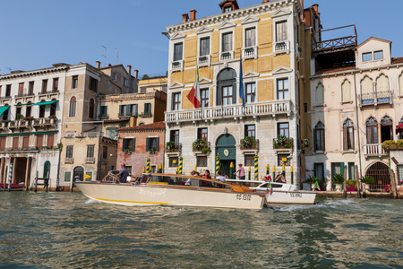 Venice, Italy - July 2, 2018: Closeup photography of motorboats with people and historical buildings of Grand Canal (Canal Grande) from gondola. Summer sunny day and blue sky