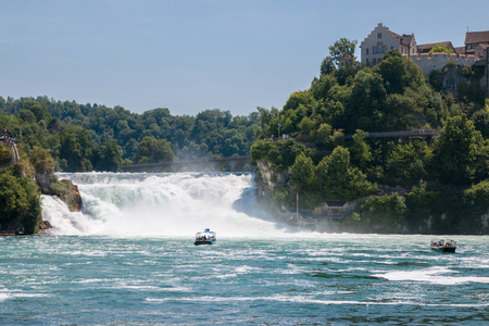 Schaffhausen, Switzerland - June 22, 2017: Boat with people floating to the waterfall the Rhine Falls. It is one of the main tourist attractions. Summer day with blue sky