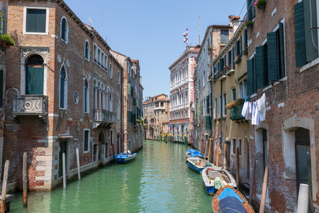 Panoramic view of Venice narrow canal with historical buildings and boat from bridge. Landscape of summer sunny day
