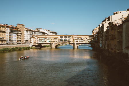 Florence, Italy - June 26, 2018: Panoramic view on Ponte Vecchio (Old Bridge) is a medieval stone closed-spandrel segmental arch bridge over Arno River, in Florence. Summer day and blue sky
