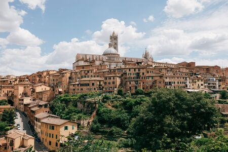 Panoramic view of Siena city with historic buildings and far away Siena Cathedral (Duomo di Siena). Summer sunny day and dramatic blue sky Reklamní fotografie