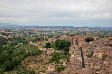 Panoramic view of Siena city with historic buildings and far away green fields from Torre del Mangia is a tower in city. Summer sunny day and dramatic blue sky Reklamní fotografie