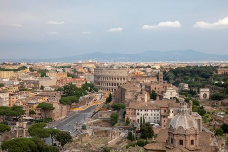 Panoramic view of city Rome with Roman forum and Colosseum from Vittorio Emanuele II Monument also known as the Vittoriano. Summer sunny day and dramatic blue sky Stock Photo