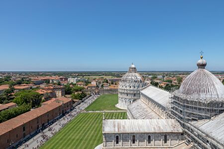 Panoramic view of Piazza del Miracoli with Pisa Baptistery of St. John and Pisa Cathedral from Tower of Pisa. People walk and rest on square 免版税图像