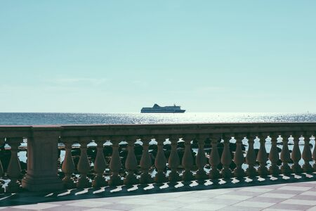 Panoramic view of Terrazza Mascagni (Mascagni terrace) in front of the Ligurian sea on the western coast of Tuscany in Livorno. People walk and rest on terrace