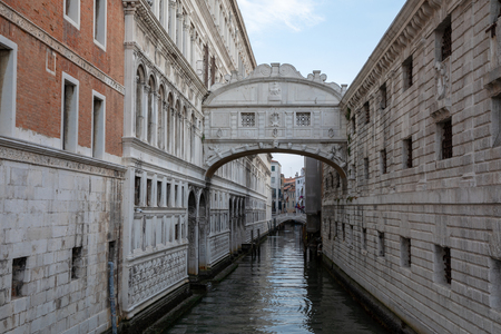 Venice, Italy - July 1, 2018: Panoramic view of Bridge of Sighs (Ponte dei Sospiri) is a bridge located in Venice on coast of city. Landscape of summer morning day and dramatic blue sky