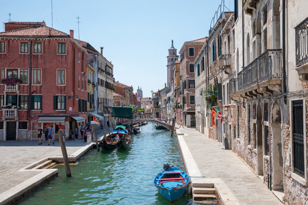 Venice, Italy - July 1, 2018: Panoramic view of Venice narrow canal with historical buildings and boats from bridge. People relax and walking. Landscape of summer sunny day