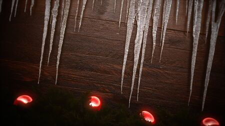 Closeup red balls and icicles on wood background. Luxury and elegant dynamic style 3D illustration for winter holiday