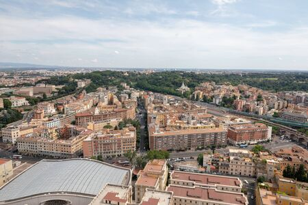 Panoramic view on city of Rome from Papal Basilica of St. Peter (St. Peter's Basilica). Summer day, people walk on street and cars on road