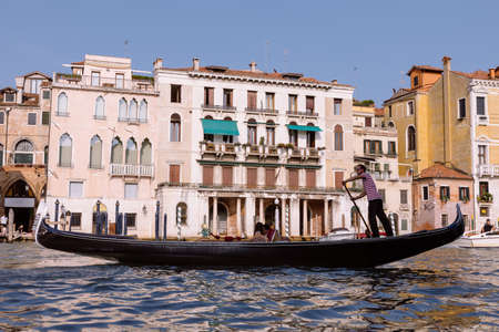 Venice, Italy - July 2, 2018: Closeup photography of gondola with people and gondolier, in the background the historical buildings of Grand Canal (Canal Grande). Summer sunny day and blue sky Editorial