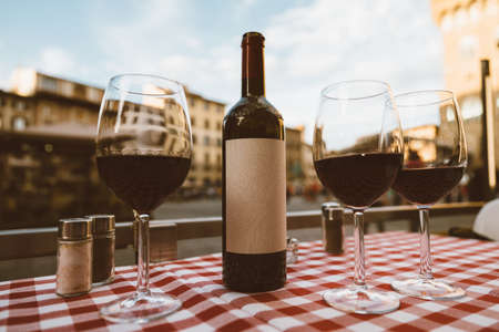 Closeup of bottle red wine and glasses on table of restaurant on background of Piazza della Signoria in summer day Imagens