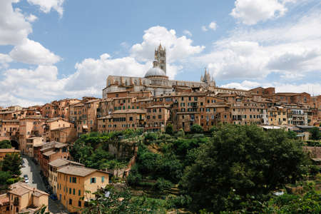 Panoramic view of Siena city with historic buildings and far away Siena Cathedral (Duomo di Siena). Summer sunny day and dramatic blue sky Imagens