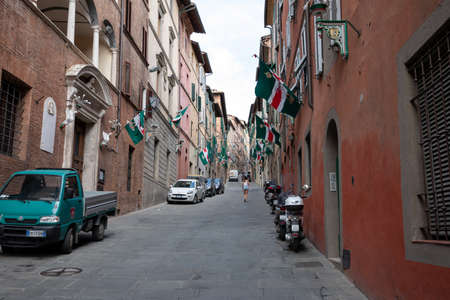 Siena, Italy - June 28, 2018: Walking on narrow street in Siena city with historic buildings and shops. Summer sunny day and blue sky Imagens