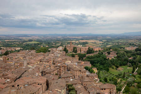Panoramic view of Siena city with historic buildings and far away green fields from Torre del Mangia is a tower in city. Summer sunny day and dramatic blue sky Imagens