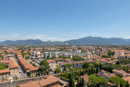 Panoramic view of Pisa city with historic buildings and far away mountains from Tower of Pisa. Summer day and sunny blue sky Imagens