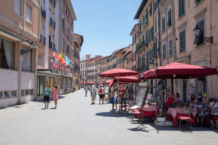 Pisa, Italy - June 29, 2018: Walking on Borgo Stretto street in Pisa city with historic buildings and shops. People walk and rest around. Summer sunny day and blue sky Editorial