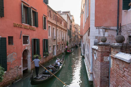 Venice, Italy - July 2, 2018: Panoramic view of Venice narrow canal with historical buildings and gondolas from bridge. Singer sings in a gondola. Summer sunny day and sunset sky