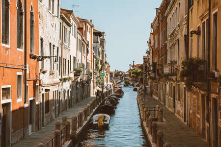 Venice, Italy - July 1, 2018: Panoramic view of Venice narrow canal with historical buildings and boats from bridge. Landscape of summer sunny day