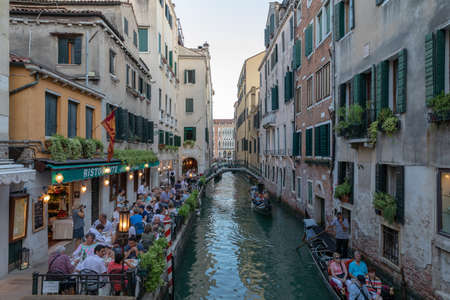 Venice, Italy - June 30, 2018: Panoramic view of Venice canal with historical buildings and gondolas from bridge. People relax and eating in restaurant. Landscape of summer evening day