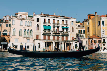 Venice, Italy - July 2, 2018: Closeup photography of gondola with people and gondolier, in the background the historical buildings of Grand Canal (Canal Grande). Summer sunny day and blue sky