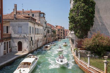Venice, Italy - July 1, 2018: Panoramic view of Venice narrow canal with historical buildings and boats traffic from Bridge Foscari. Landscape of summer sunny day and blue sky Editorial
