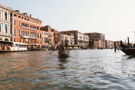 Venice, Italy - July 2, 2018: Panoramic view of Grand Canal (Canal Grande) from gondola with active traffic gondolas. Grand Canal it is forms one of the major water-traffic corridors in Venice city Editorial