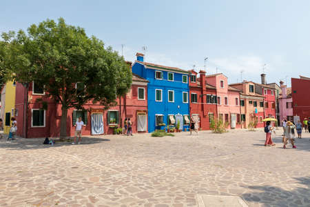 Burano, Venice, Italy - July 2, 2018: Panoramic view of brightly coloured homes of Burano is an island in the Venetian Lagoon. People walk and rest on streets. Summer sunny day and blue sky Editorial