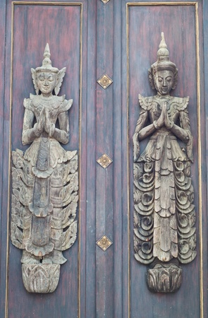 Two angel woodcraft on wooden door  photo