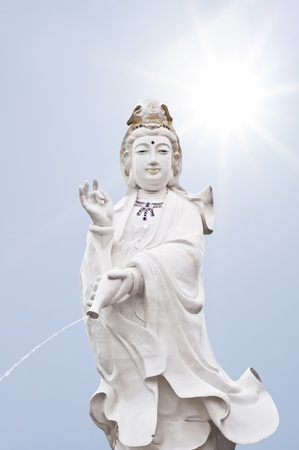 Quan Yin statue in sunlight and blue sky  Stock Photo