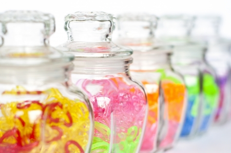 Colorful plastic hearts in glass bottles