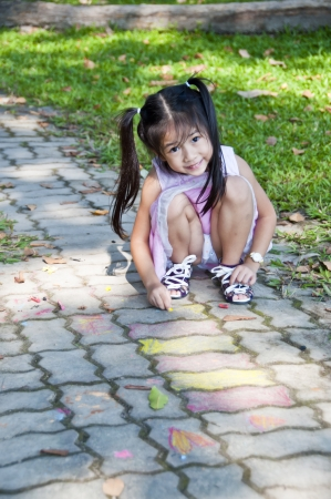 Little asian pretty girl drawing on footpath  photo