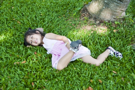 Little asian pretty girl lying on green grass  photo