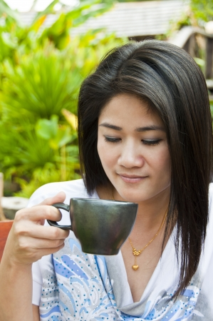 Beautiful asian woman with a cup of coffee  Stock Photo - 16797596