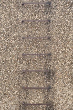 Steel ladder in gravel wall  Stock Photo - 17097487