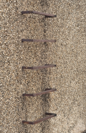 Steel ladder in gravel wall  Stock Photo - 17097484
