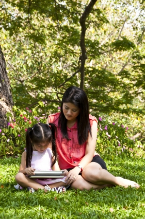 Little asian girl and mom enjoy tablet PC  photo