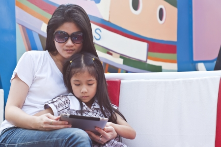 Little asian girl and mom enjoy tablet PC in shopping mall  photo