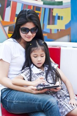 Petite fille asiatique et la mère de profiter de PC tablette dans un centre commercial