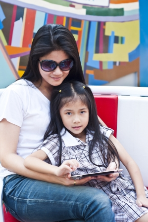 Little asian girl and mom enjoy tablet PC in shopping mall