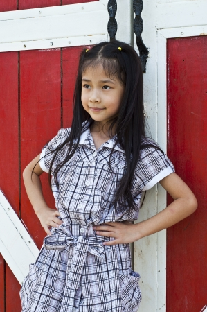 Little asian girl posing in front of red wooden door  Stock Photo - 18448486