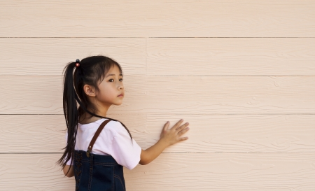 Little asian girl posing at wooden wall  Stock Photo - 18654716