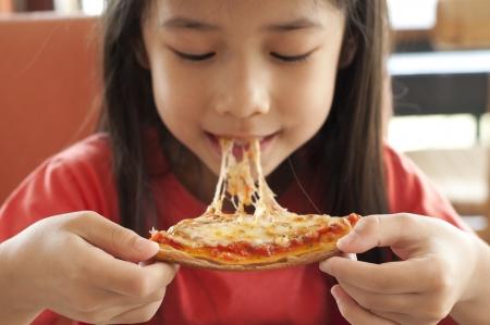 eten: Weinig Aziatisch meisje genieten van pizza Stockfoto