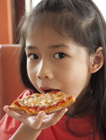 Little Asian girl enjoy pizza  photo