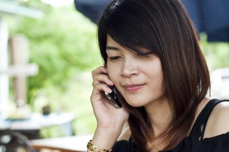 Beautiful Asian woman using mobile phone  Stock Photo