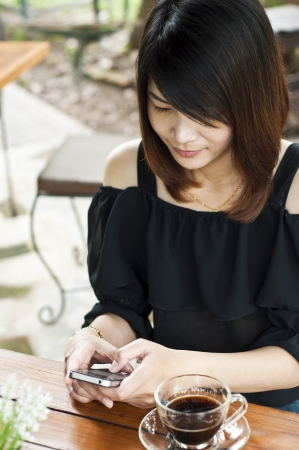 Beautiful Asian woman relaxing in coffee break with mobile phone  Stock Photo