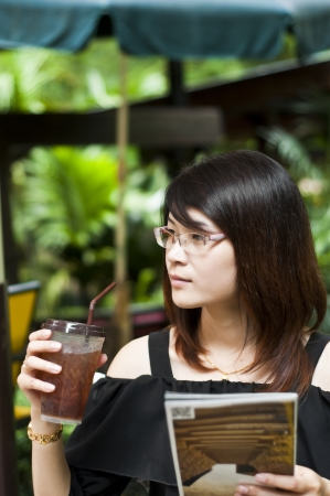 Beautiful Asian woman enjoy iced tea and holding travel guide map  photo