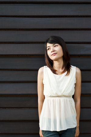 Beautiful Asian woman posing at wooden wall