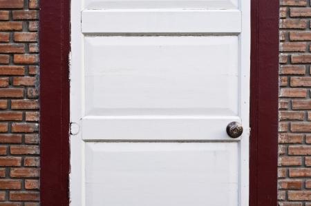 White wooden door on brick wall  Stock Photo