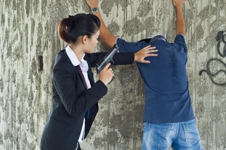 Suspect under arrest by policewoman  photo
