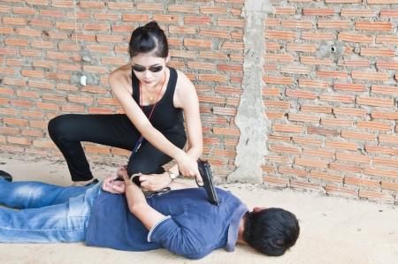 mujer policia: Sospechoso detenido por la polic�a Foto de archivo